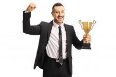 Procurement Manager holding a trophy
